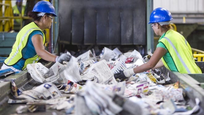 Workers remove plastic bags moving down a conveyor belt at the North Gateway Transfer Station recycling facility. Despite many efforts to educate the public, many people still put plastic bags in their recycling bins, creating a multitude of problems for the recycling plants. The bags clog machines and contaminate some items that could be recycled otherwise.