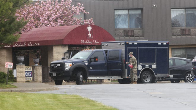 A soldier with the National Guard is seen in front of the entrance to the Andover Subacute and Rehabilitation II building on May 8.