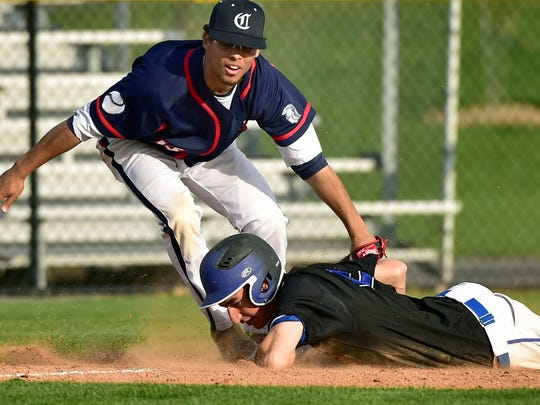 Chambersburg's Carlin Christian, left,  can't get the tag down in time to catch Bubba Hamilton, advancing to third base. Waynesboro defeated Chambersburg 14-6 during their game Friday, April 1, 2016.