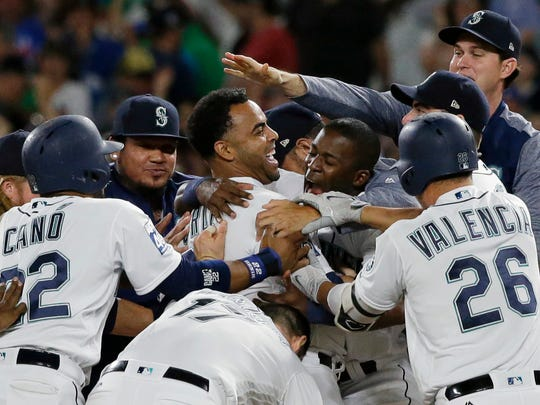 Seattle Mariners' Nelson Cruz, center, is mobbed by teammates after he hit a walk-off single to score Ben Gamel during the 10th inning of the team's baseball game against the New York Yankees, Saturday, July 22, 2017, in Seattle. The Mariners won 6-5.