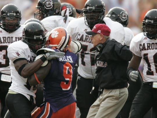 A fight breaks out between South Carolina and Clemson benches as USC head coach Lou Holtz tries to break it up late in the fourth quarter Saturday, November 20, 2004 at Clemson's Memorial Stadium.