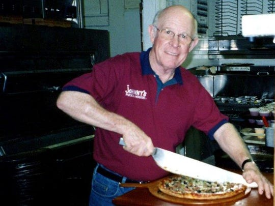 Johnny Huntsman cuts the last pizza made at the flagship Johnny's Pizza House location on DeSiard Street in Monroe in November 2001.