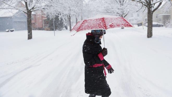 Dandan Guo walks through the snow along E. Second Street in Flint on Wednesday, February 24, 2016.