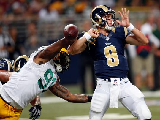 Green Bay Packers linebacker Jayrone Elliott, left, knocks the ball out of the hand of St. Louis Rams quarterback Austin Davis during the fourth quarter of an NFL preseason football game Saturday, Aug. 16, 2014, in St. Louis. Davis recovered the ball but the Packers went on to win 21-7. (AP Photo/Scott Kane)