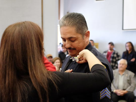 Sergeant Luis Bravo receives his badge from his wife Eva at the ceremony on Wednesday.