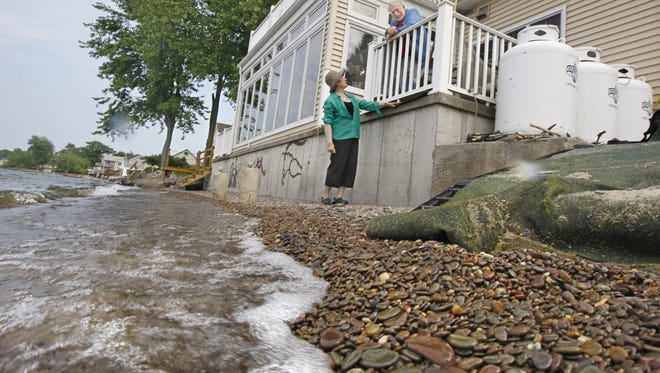 Cheryl and Bob Stevens at their lakeshore home in Hilton Tuesday, June 17, 2014.  The Stevens say that on windy days, the waters of Lake Ontario crash right against their house.