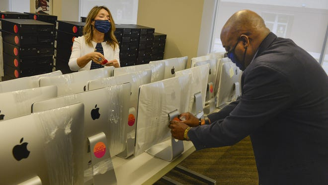 SCAD president Paula Wallace along with Mayor Van Johnson put SCAD/City of Savannah stickers on the back of donated computer equipment to help distance learning in public schools.