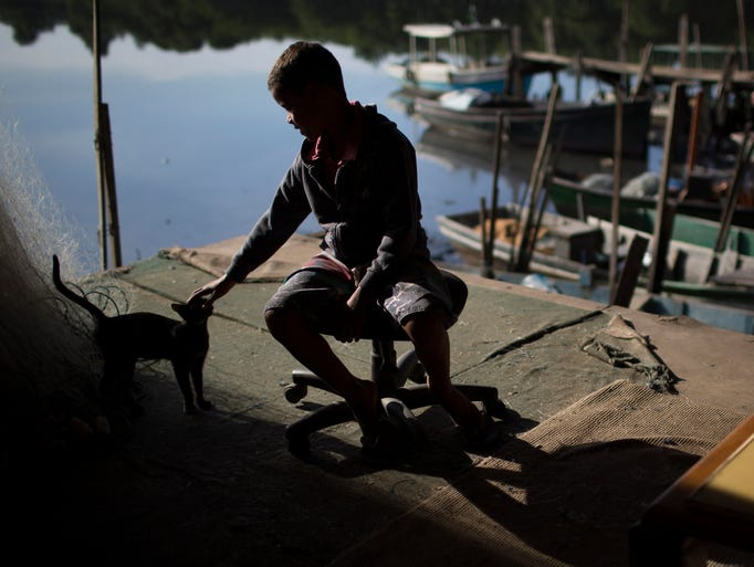 "A boy plays with a stray cat during a police operation to occupy the Vila Pinheiro, part of the Mare slum complex in Rio de Janeiro, Brazil. The Mare complex of slums, home to about 130,000 people and located near the international airport, is the latest area targeted for the government's ""pacification"" program, which sees officers move in, push out drug gangs and set up permanent police posts."