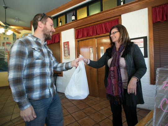 Consider Delivery driver Jared Selders picks up a delivery from A Bite of Belgium owner Sandy Murray on Thursday.
