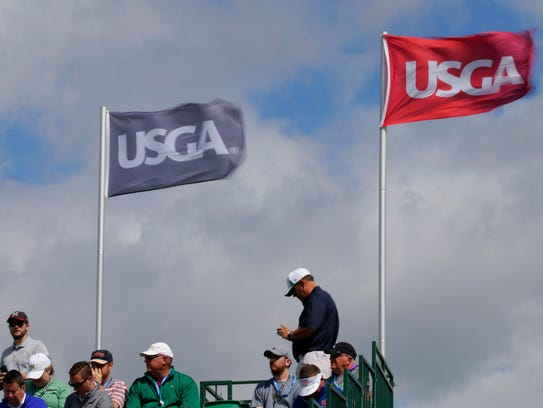 Wind whips the USGA flags on the grandstands on No.