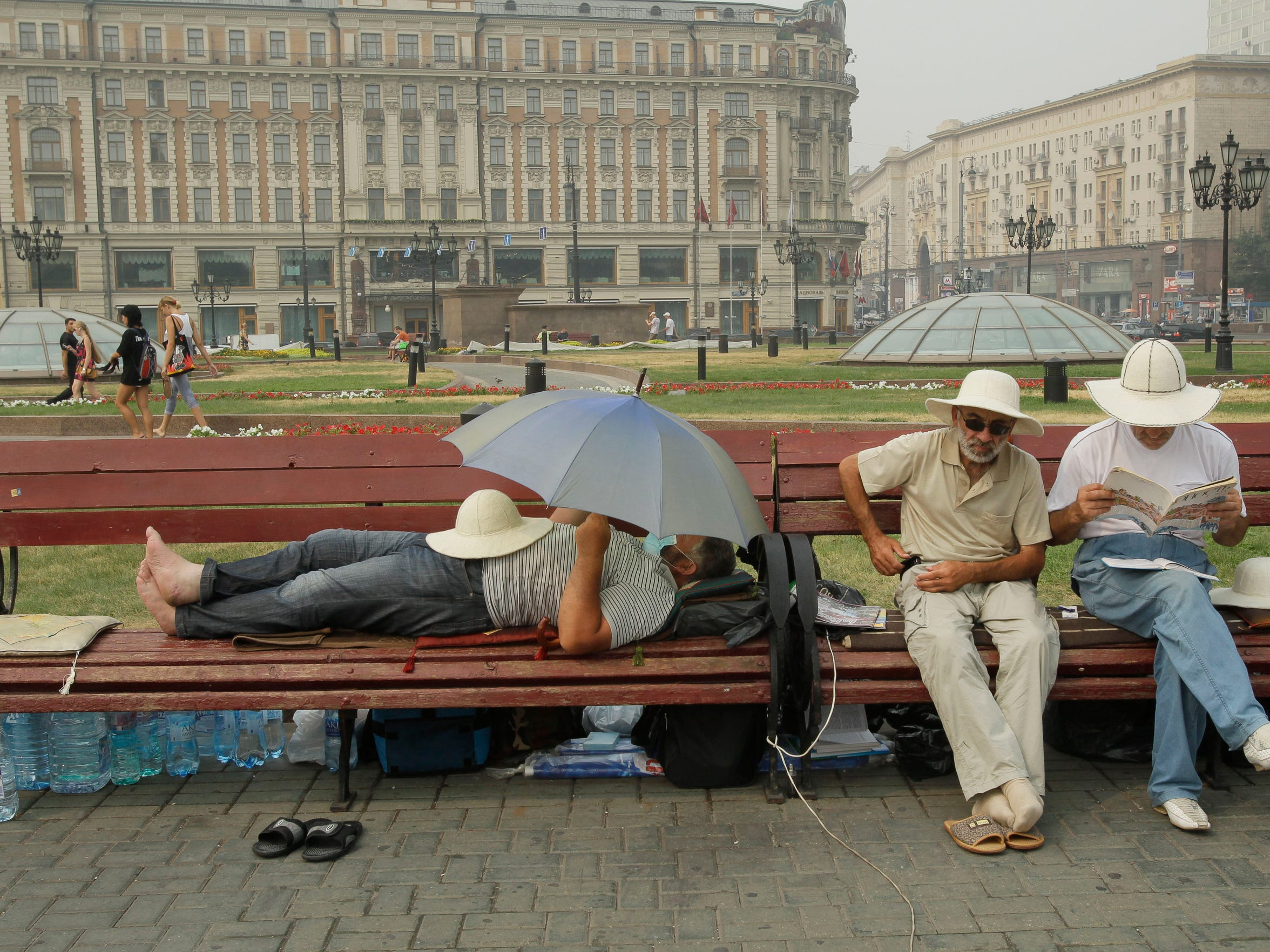 People rest at Manezhaya Square, just outside the Moscow Kremlin, on Aug. 9, 2010, enjoying a brief respite from smog due to a change in the wind direction. Deaths in Moscow doubled to an average of 700 people a day as the Russian capital was engulfed by poisonous smog from wildfires and a sweltering heat wave.