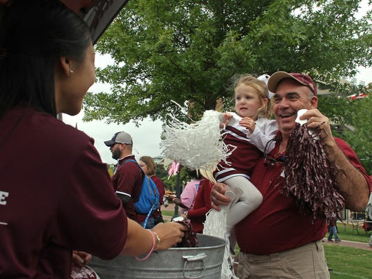 Van Tong, left an Mississippi State graduate student passes out pom-poms to Tom Monroe, right and his 2-year-old granddaughter Scout Monroe from Brookhaven, Miss., prior to the NCAA college football game between Troy and Mississippi State in Starkville, Miss., Saturday, Oct 10, 2015,  (AP Photo/Jim Lytle)