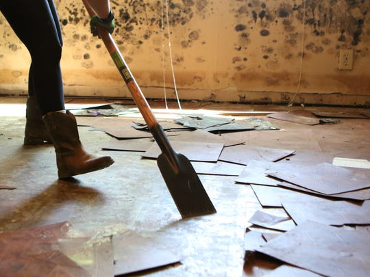 Keller Williams employee Pamela Petrus scrapes tiles
