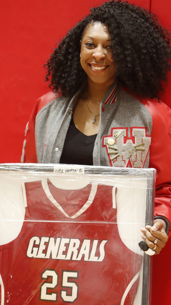 Former Wade Hampton basketball standout Alexis Dillard poses with her No. 25 jersey that was retired by the school Friday night.
