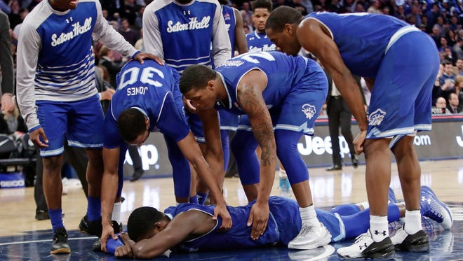 Seton Hall's Angel Delgado, bottom, is consoled by teammates after an NCAA college basketball game against Villanova during the Big East men's tournament