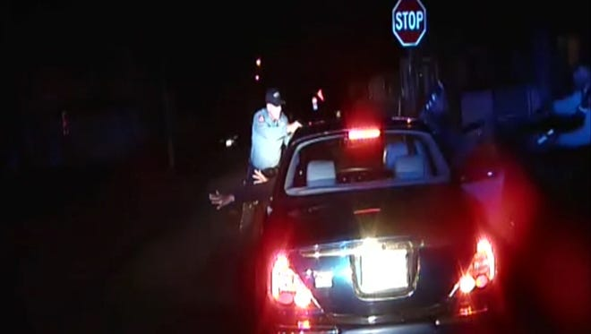 In this frame grab from an officer's dashboard camera taken Dec. 30, 2014, and provided by the Bridgeton, N..J. Police Department, police officers Braheme Days and Roger Worley stand near a car they pulled over for running a stop sign in Bridgeton. One of the officers warned his partner that he could see a gun in the glove compartment. The nearly two-minute standoff resulted in the death of Jerame Reid, one of two men in the car. (AP Photo/Bridgeton Police Department)