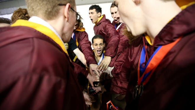 Kingston's Quincy Walker (center) and his team gather for a team cheer as their first place team finish in the 2A Swim/Dive Championships is announced at King County Aquatic Center inis announced on Saturday, Feb. 18, 2017.