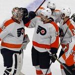 Philadelphia Flyers' Luke Schenn (22) congratulates goalie Steve Mason (35) on an overtime win against the Carolina Hurricanes, Saturday, Nov. 14, 2015, in Raleigh, N.C. The Flyers won 3-2. (AP Photo/Karl B DeBlaker)