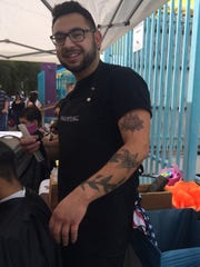 Juan Carlos Montes De Oca cuts hair at the Free on Fourth wellness fair in Tucson on March 16, 2018. Montes De Oca was being investigated by the cosmetology board for giving haircuts to homeless veterans. Gov. Doug Ducey asked the board to stop its investigation.