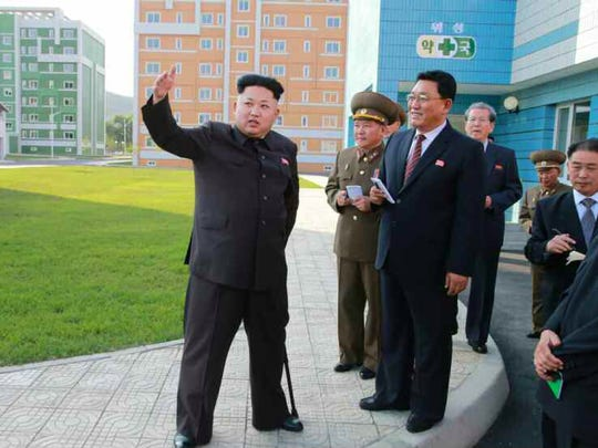 This picture taken from North Korean paper Rodong Sinmun on October 14, 2014 shows North Korean leader Kim Jong Un (left) during an inspection tour of a newly-built housing complex in Pyongyang.