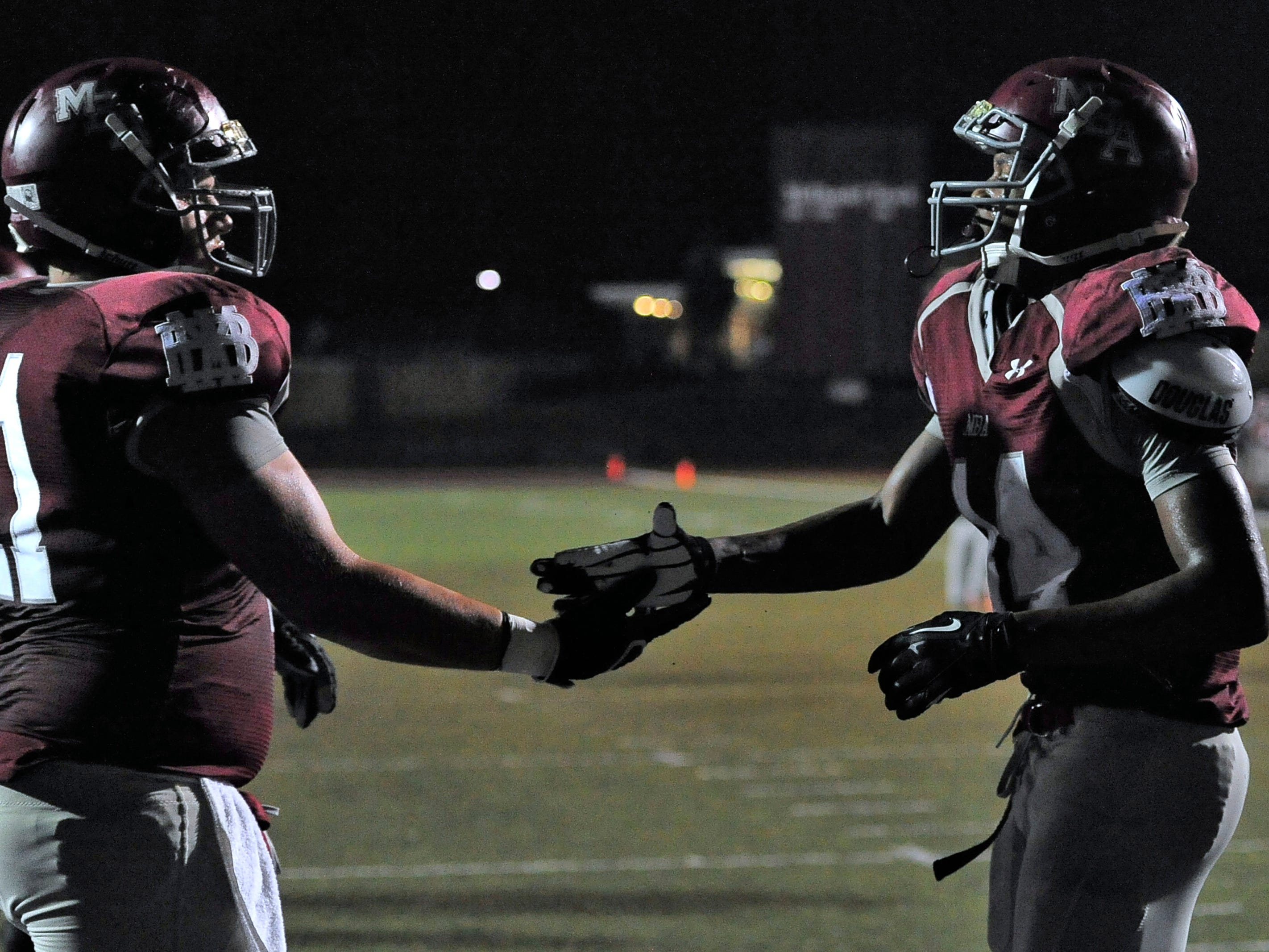 MBA offensive lineman Joseph Scowden congratulates running back Ty Chandler after a touchdown vs. rival Father Ryan Friday.