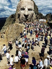 Hikers on the annual Volksmarch up the Crazy Horse mountain carving in the Black Hills of S.D. were among the first to see the emerging face with the mouth blocked out in this photo from Sep 5, 1997.