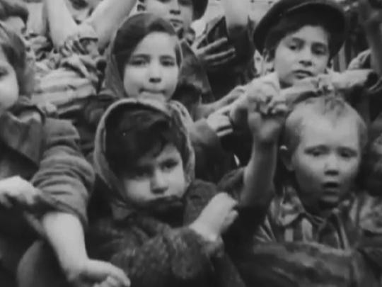 The photo that sparked the reunion of three child survivors of Auschwitz. Michael Bornstein is the boy to the right, Sarah Ludwig is next to him to the right and Tova Friedman is diagonally above Ludwig to the right. with other children showing number tattoos  All three live in New Jersey and reunited on June 11 for the first time in 72 years.
