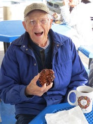 Jack Sherman poses with an apple fritter and a cup