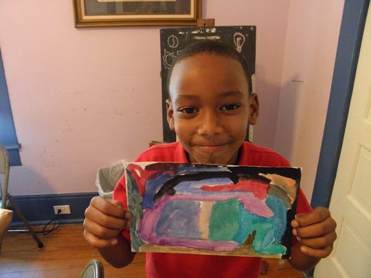 Renzi Education and Art Center student makes abstract painting.