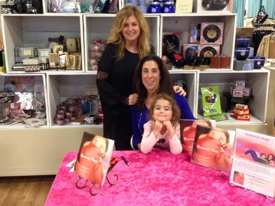 Barbara Adoff (center) showcases her 'Grammy's Hugs' book with granddaughter Iva and Michelle Stander of Mixellaneous in Marlton.