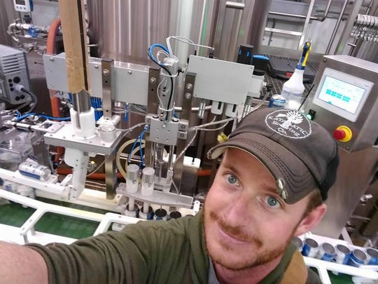 Tony Reindl of the Montana Canning Co. snaps a selfie as he cans Badlands Extra Pale IPA from Meadowlark Brewing. Reindl's canning business is mobile, traveling to breweries across the state.
