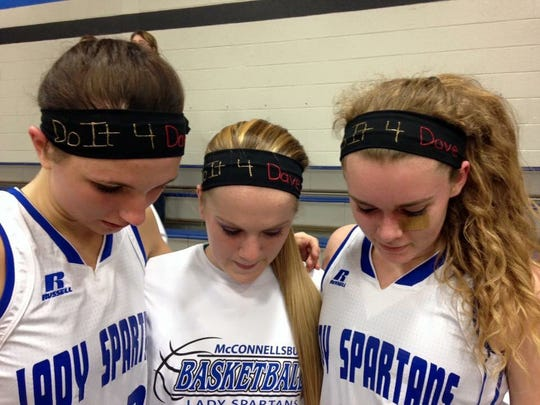 """McConnellsburg players, from left, Bronwyne Mellott, Justice Seville and Bridgette Ritchey show off headbands with the words """"Do It 4 Dave,"""" which the Spartans made following the death of assistant coach Dave Hoover. Hoover was also the coach of Forbes Road in the first all-Fulton County District 5 championship."""
