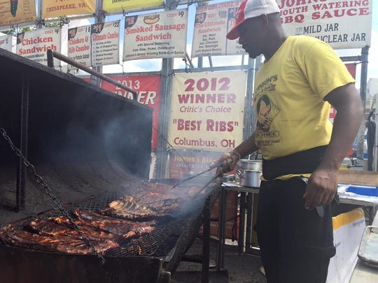 An employee from Johnson's Bar-BQue turns ribs on a grill.