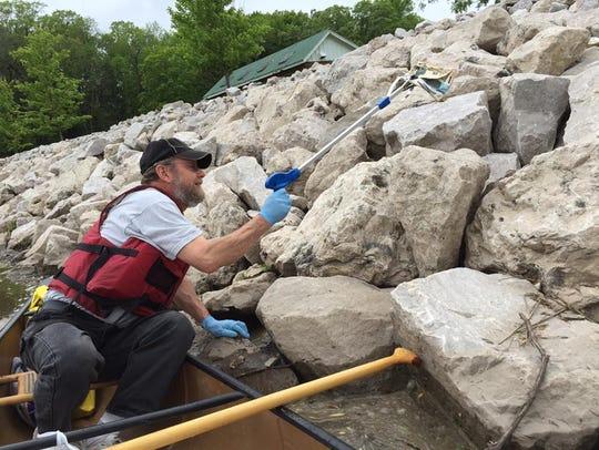 Volunteer Steve Lutzke picks up debris on shore during