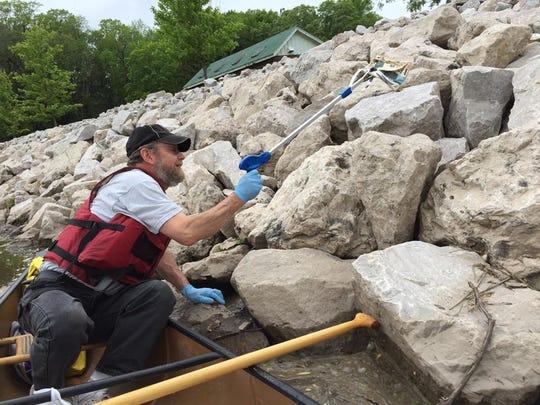Volunteer Steve Lutzke picks up debris on shore during a June 4 cleanup of the Manitowoc River.