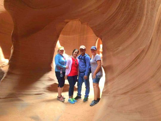 Nancy Mitchell, left, and Kim and Kao Virak stopped with a fourth traveling companion at Antelope Canyon carved by weather and water east of Page, Ariz. The slot canyon is considered sacred by the Navajo.