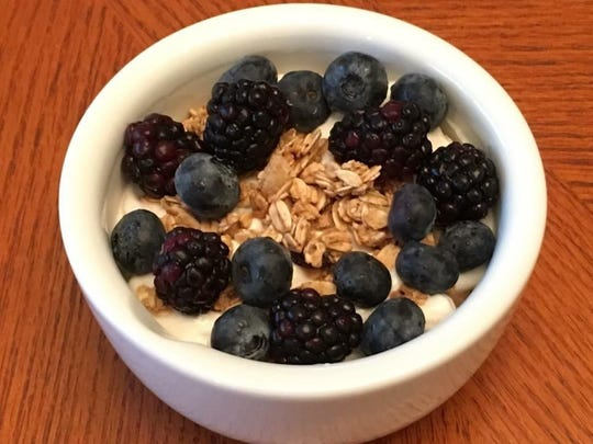 Plain Greek yogurt seasoned with cinnamon and honey, topped with low fat granola, blackberries and blueberries.