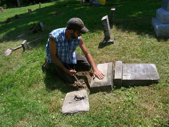 George Stull pieces a headstone in King-Stull cemetery back together at a Virginia Volunteers of the Confederacy event.