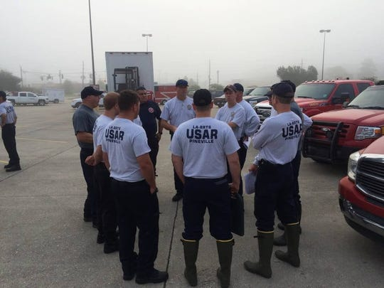 Members of the Region 6 Urban Search & Rescue, including personnel from the Pineville, Alexandria, Natchitoches and Rapides Parish No. 2 fire departments, are briefed about operations before going on search-and-rescue missions to flooded areas of Walker, which is east of Baton Rouge.