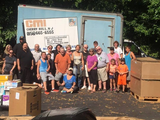 Volunteers stand near boxes they helped pack at CMI