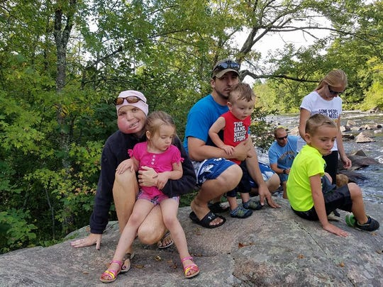 Lindsay Zuelke, left, holds her daughter Danica next to her husband Nathan and their son Easton on a family vacation this summer.