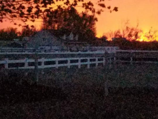 A submitted photo of flames behind a home with a white picket fence from the Little Valley Fire, which sparked early Friday morning in Washoe County Valley.