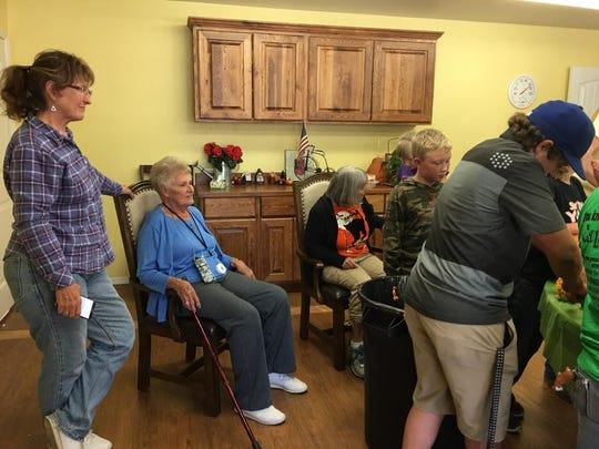 Good Life Senior Center residents look on as Capitan 4-H members carve pumpkins Sunday.
