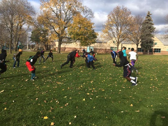 Milwaukee police officers and teens play flag football at Sherman Park Saturday.