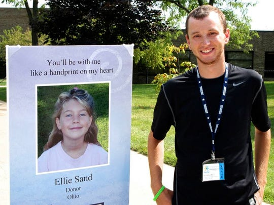 Daniel Repp stands next to a memorial photo of Ellie Sand who posthumously donated a life-saving kidney to Repp.