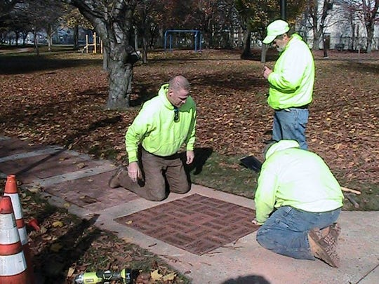 Gloucester City public works crews lay the first set of inscribed bricks to be unveiled Saturday at a ribbon-cutting and dedication in Proprietors Park.