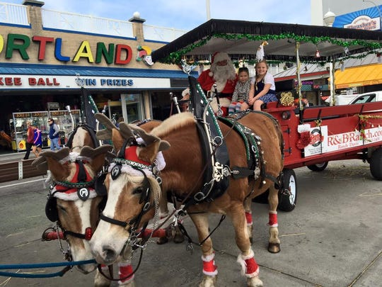 Children enjoy a ride with Santa and his two horses, Jake and Bonnie.