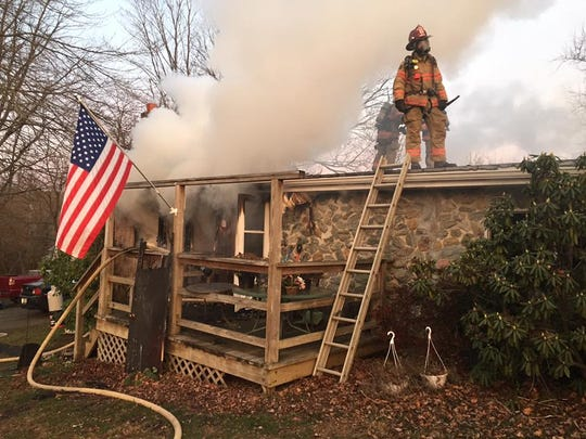 A firefighter works on the roof of a mobile home that burned in Peach Bottom Township on Saturday.