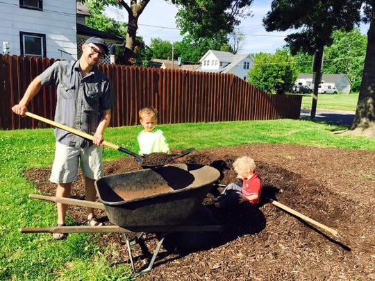 A family from Woodland Heights Neighborhood Association plants in the neighborhood garden. The association is very active and uses Facebook and Nextdoor to reach neighbors.
