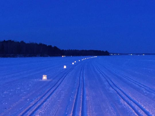Hundreds of ice luminaries mark the Book Across the Bay Course across frozen Lake Superior.